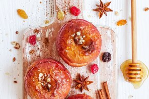 Red baked apples with cinnamon, walnuts and honey. Autumn or winter dessert.
