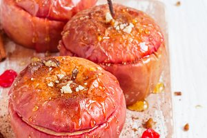 Red baked apples with cinnamon, walnuts and honey. Healthy Diet Dessert.
