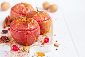 Red baked apples with cinnamon, walnuts and honey on a white background. Autumn or winter dessert