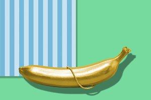 Gold banana on bright abstract back