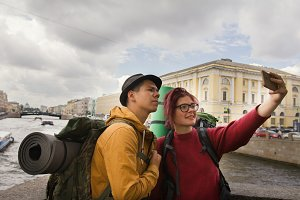 Young couple of tourists taking selfies against the background of the city