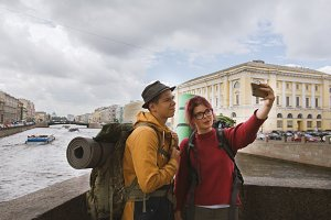A couple of tourists taking selfies against the background of architecture