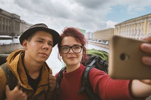 Young couple of tourists taking selfies against the background of architecture