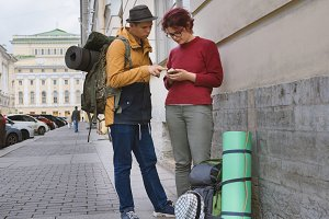 Young couple of tourists exploring city guide in phone