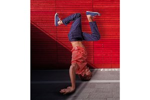 Break dancer doing handstand against red wall background