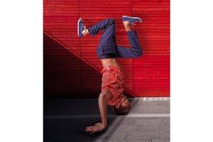 Break dancer doing handstand against red wall background
