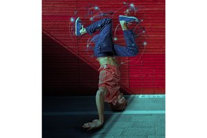 Break dancer doing handstand against colorful wall background
