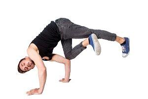 Break dancer doing handstand against  white background