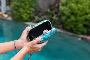 Closeup of woman hand holding fashion snakeskin python bag near the tropical swimming pool.