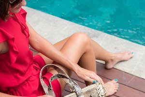Fashionable woman in red dress holding leather snakeskin python bag. Elegant outfit. Close up of purse in hands of stylish lady. Model posing near the swimming pool.