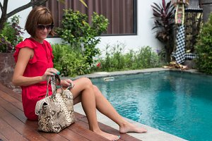 Fashionable woman holding leather snakeskin python bag. Elegant outfit. Close up of purse in hands of stylish lady. Model posing near the swimming pool.