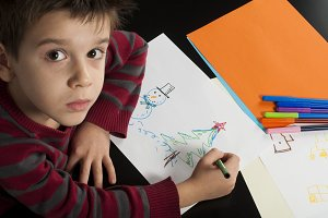 Boy drawing with markers