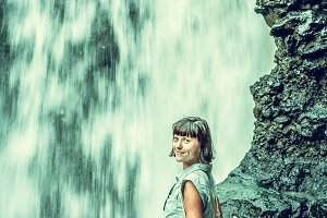 Woman on a waterfall deep in the tropical rain forest of Ubud, tropical Bali island, Indonesia. Exotic scene of tropics. Freedom concept.