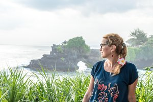 Woman on a background of Pura Tanah lot temple, Bali island, Indonesia.