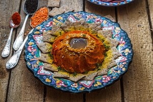 Traditional hummus of red lentil with olive oil and spices, in a traditional colourful plate, rusks and cured meat. Wooden background.