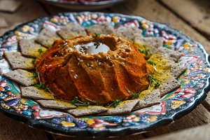 Red lentil hummus in traditional plate on the wooden table