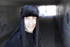 smiling young man in a subway tunnel