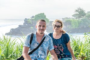 BALI, INDONESIA - MAY 4, 2017: Woman and her son on a background of Pura Tanah lot temple, Bali island, Indonesia.