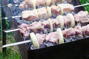 Marinated shashlik or shish kebab, raw meat grilling on metal skewer, close up. Selective focus