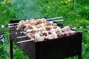 Marinated shashlik or shish kebab, raw meat grilling on metal skewer, close up. Selective focus