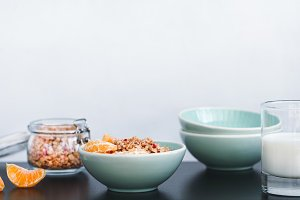 Green ceramic bowl with granola with dried berries and fresh tangerine on the black table against white wall. Healthy breakfast concept. Negative space.