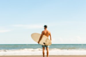 Handsome man with surf on beach.