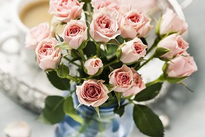 Romantic setup with coffee and roses in vase