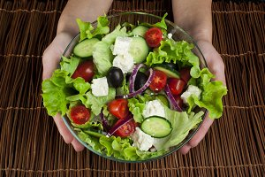 Hands holding salad in a glass bowl