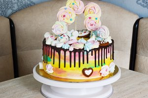 Children's cake rainbow color on a white background with wood meringue