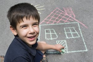 Child drawing sun and house on aspha