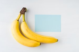 Two bananas on white with blue card