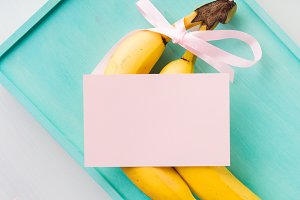 Two bananas with pink ribbon and card