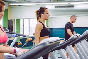 Woman with earphones training over a treadmill