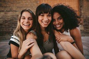 Three beautiful smiling girlfriends