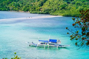 Beautiful view of a tropical island Snake with white traditional banca boat full tourists. El Nido, Palawan, Philippines