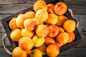 Raw apricots in wooden box