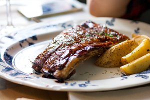Delicious grilled pork ribs with barbecue sauce, over old ceramic plate