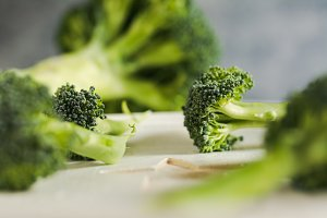 Small pieces of raw broccoli on white wood, Close up
