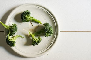 Piece of raw broccoli on white wood, From above