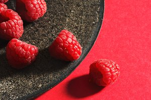Fresh raspberries on black plate