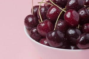 White bowl of fresh red cherries on a pink background. close-up