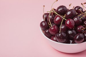 White bowl of fresh red cherries on a pink background. Copy space. close-up