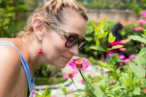 Woman sniffing flowers outdoors in the park of tropical exotic Bali island, Indonesia.