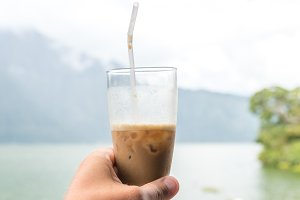 Man hand holding Iced coffee or caffe latte on a mountain background. Bali island.