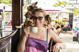 Senior woman drinking coffee in pool bar. Tropical Bali island, Indonesia.