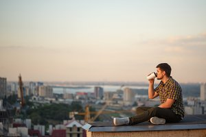 Man is drinking coffee on roof