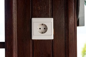 White old plastic power socket on a wooden wall outside. Bali.