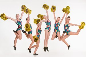 The group of teen cheerleaders jumping at white studio
