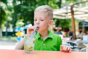 Cute little blond boy in cafe drinking cocktail mojito