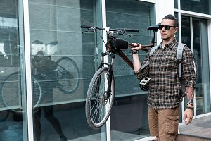 Confident young handsome man with glasses carries a bicycle on his shoulder and looks forward